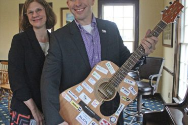This colorful guitar proudly displays the logos of NUCA Middle Tennessee's founding companies
